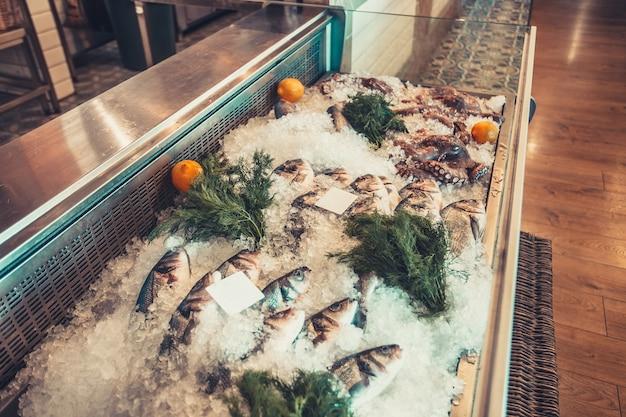 Вкусные свежие морепродукты на льду с зеленью и лимонами