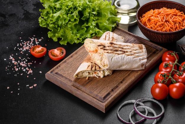 暗いコンクリートのテーブルの上に肉と野菜を添えたおいしい新鮮なシャワルマ。ファーストフード、トルコ料理