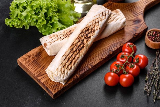 Вкусная свежая шаурма с мясом и овощами на темном бетонном столе