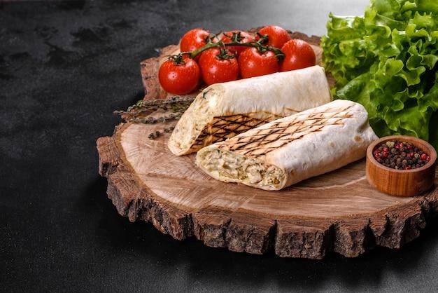 暗いコンクリートのテーブルの上に肉と野菜を添えたおいしい新鮮なシャワルマ