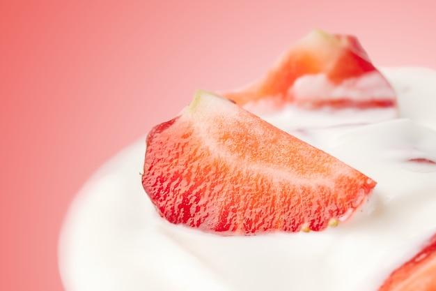 Delicious fresh strawberry falling into glass with yogurt