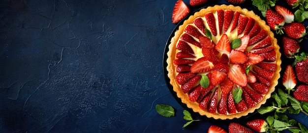 Delicious fresh strawberry tart on trendy dark blue background