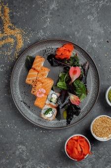 ダークストーンのテーブルの灰色のプレートにサーモンとフィラデルフィアチーズを添えたおいしい新鮮な巻き寿司。伝統的な日本のシーフード、健康食品のコンセプト。
