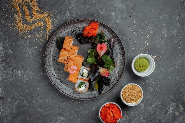 グレーのプレートにサーモンとフィラデルフィアチーズを添えたおいしい新鮮な巻き寿司。伝統的な日本のシーフード、健康食品のコンセプト。