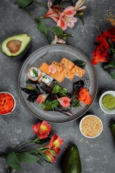 Delicious fresh sushi rolls with salmon and philadelphia cheese on gray plate on dark stone background