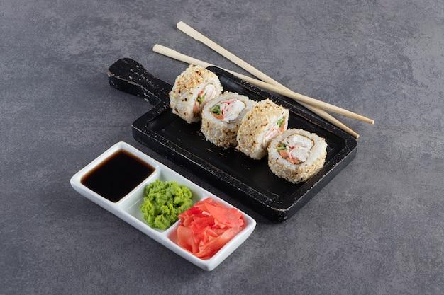 Deliziosi rotoli di sushi freschi con semi di sesamo sul tagliere nero.