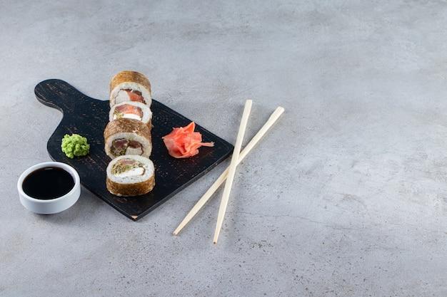 Вкусные свежие суши-роллы с соевым соусом и деревянными палочками на деревянной доске.
