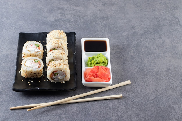 Delicious fresh sushi rolls with soy sauce placed on stone surface.