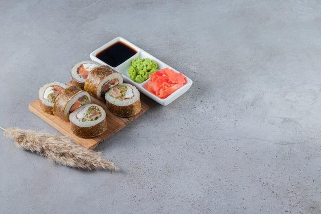 Deliziosi involtini di sushi freschi con salsa di soia su tavola di legno.