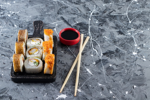Delicious fresh sushi rolls with soy sauce and wooden chopsticks placed on a dark wooden board .