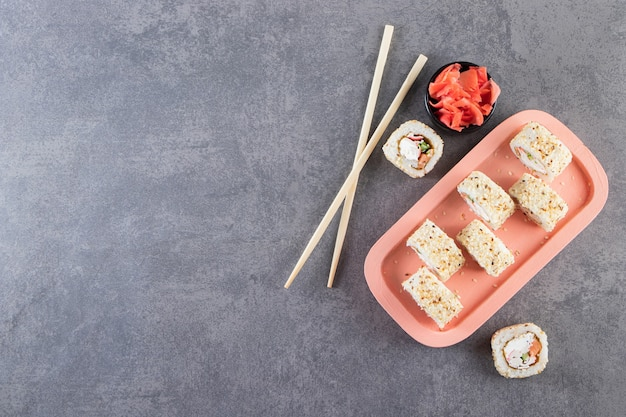 Delicious fresh sushi rolls with soy sauce and wooden chopsticks placed on a wooden board .