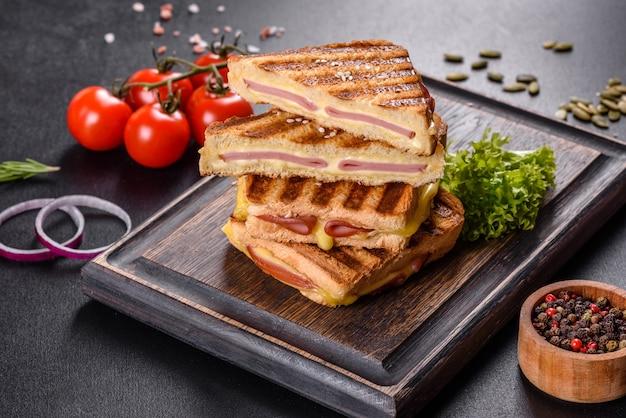 Вкусные свежие тосты на гриле с сыром и ветчиной. бутерброды, быстрые закуски