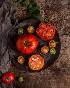 Вкусные свежие помидоры на тарелке над видом
