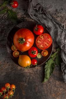 Вкусные свежие помидоры на тарелке, вид сверху