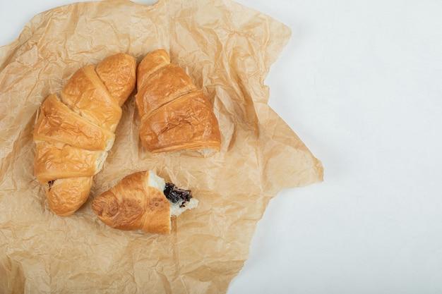 Deliziosi due croissant freschi su carta pergamena.
