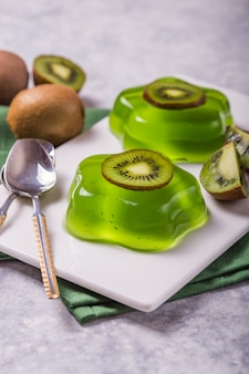 Delicious fresh two green jelly with kiwi slices on concrete table
