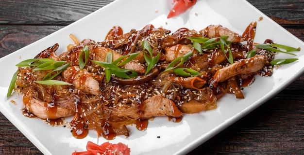 Вкусный свежий удон с курицей и рисовой лапшой со специями и зеленью