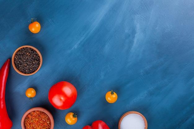 Deliziose verdure fresche e vari condimenti sulla superficie blu.