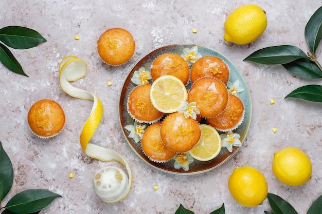 Muffin al limone casalinghi di recente al forno deliziosi con i limoni su un piatto su luce