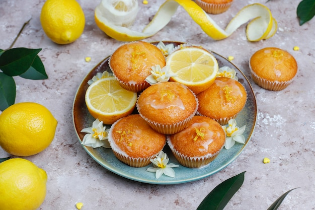 Delicious freshly baked homemade lemon muffins with lemons on a plate on light