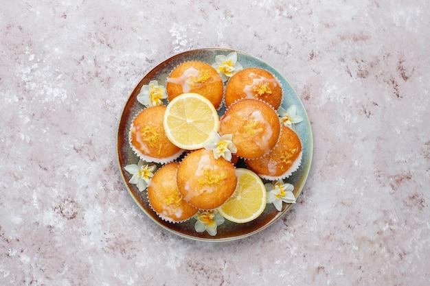 Muffin casalinghi di recente al forno deliziosi del limone con i limoni su un piatto sulla tavola