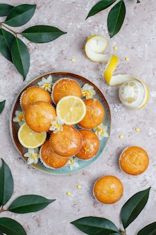 Delicious freshly baked homemade lemon muffins with lemons on a plate on table