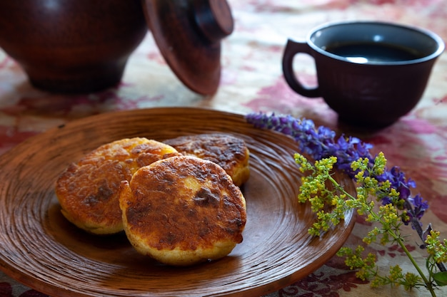 Delicious fried cheesecakes on a clay plate in a rustic setting with wildflowers.