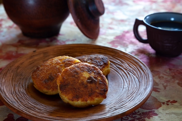 Delicious fried cheesecakes on a clay plate in a rustic setting.