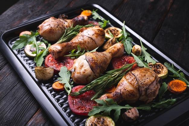 Вкусные жареные куриные ножки на сковороде, чипсы, фаст-фуд, овощи на гриле крупным планом