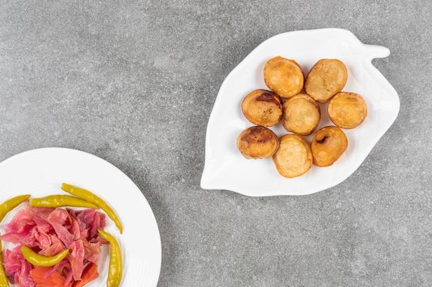 Deliziosi gnocchi fritti sul piatto bianco con sottaceti