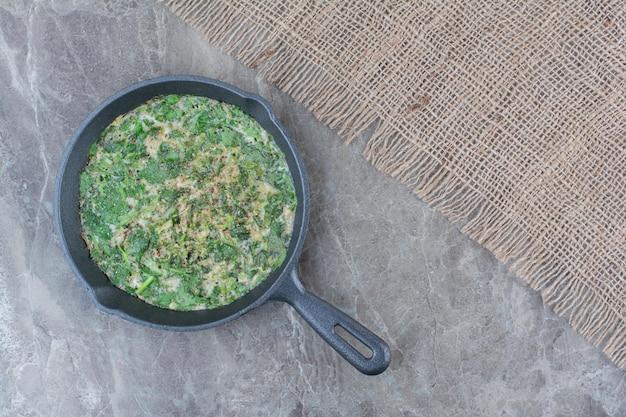 Вкусная яичница с зеленью на темной сковороде на мешковине. фото высокого качества
