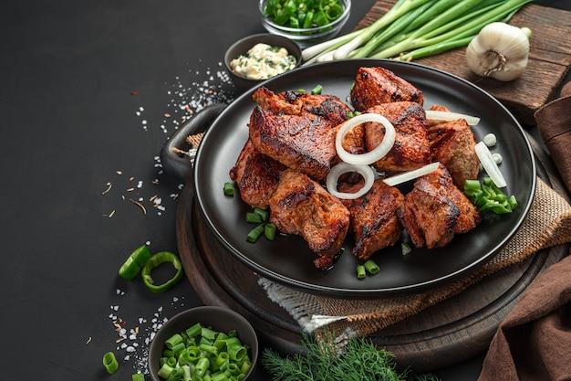 허브, 소스, 향신료와 함께 검은 배경에 양파와 함께 맛있는 튀긴 고기. 측면 보기, 복사를 위한 공간입니다.