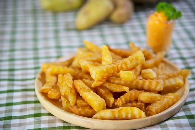 담근 소스와 함께 나무 접시에 맛있는 튀긴 감자-전통적인 패스트 푸드 개념