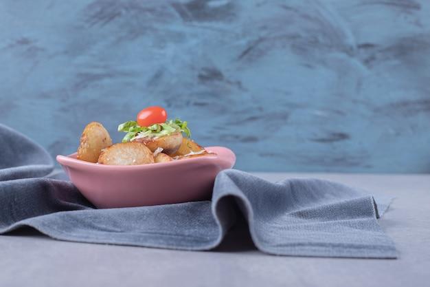Deliziose patate fritte in ciotola rosa.