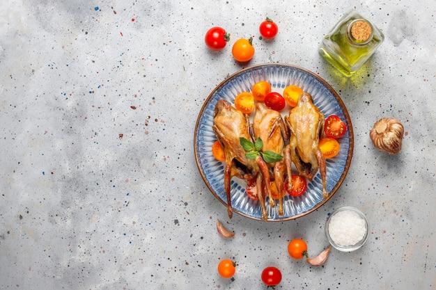Deliziosa quaglia fritta con erbe e pomodorini.