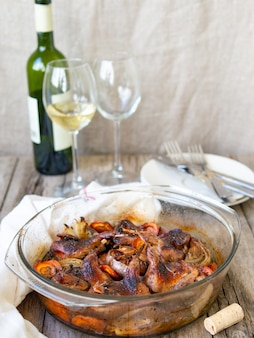 Delicious fried quails with vegetables - garlic, carrots, onions , baked in a glass form, bottle of wine and two glasses