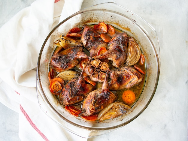 Delicious fried quails with vegetables - garlic, carrots, onions , baked in a glass form