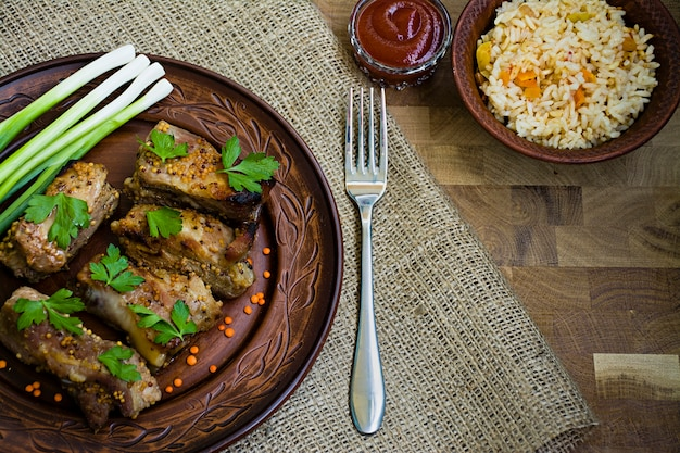 Delicious fried ribs, dressed with honey sauce, decorated with greens and vegetables