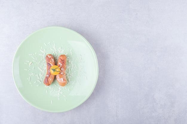 맛있는 튀긴 된 소시지와 녹색 접시에 체리 토마토.