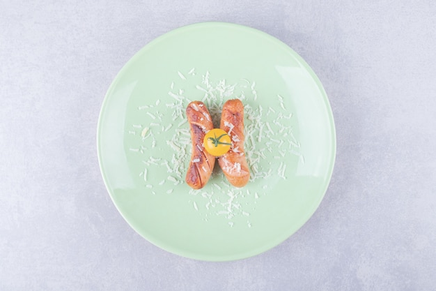 Deliziose salsicce fritte e pomodorini sul piatto verde.