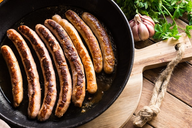Delicious fried sausages with golden crust in iron cast pan, fresh parsley garlic on wood table