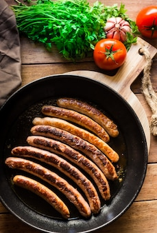 Delicious fried sausages with golden crust in iron cast pan, fresh parsley tomatoes on wood table