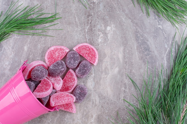 Delicious fruit jelly candies out of pink bucket on stone.
