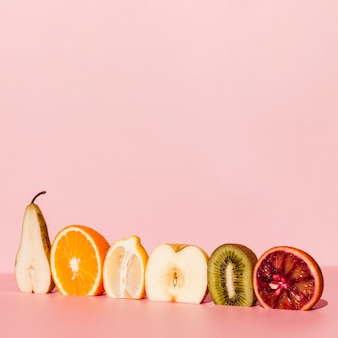 Delicious fruits on pink background