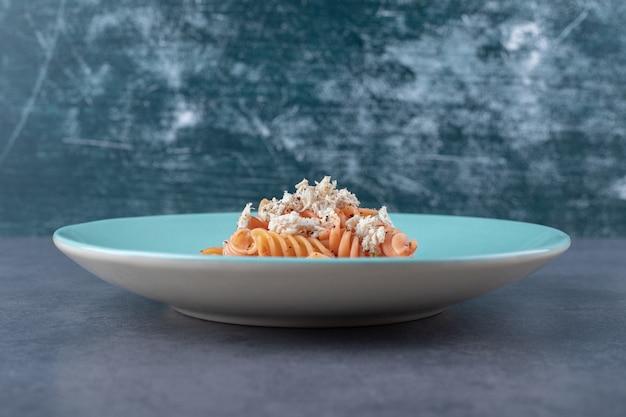 Вкусные макароны и морковь фузилли на синей тарелке.