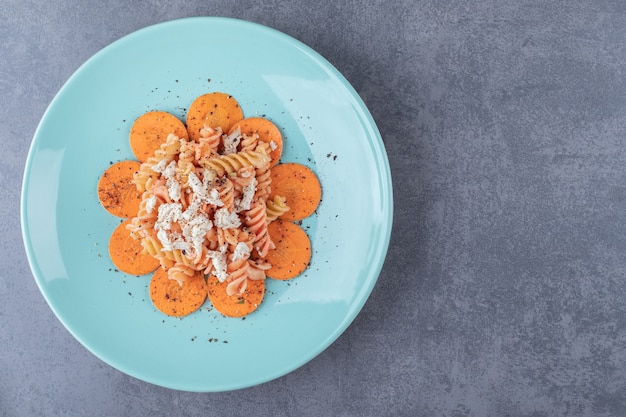 맛 있는 fusilli 파스타와 당근 블루 접시에.