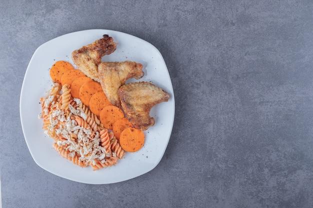 Вкусные макаронные изделия фузилли и куриные крылышки на белой тарелке.