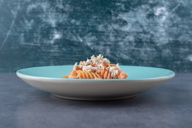 Delicious fusilli pasta and carrot on blue plate.