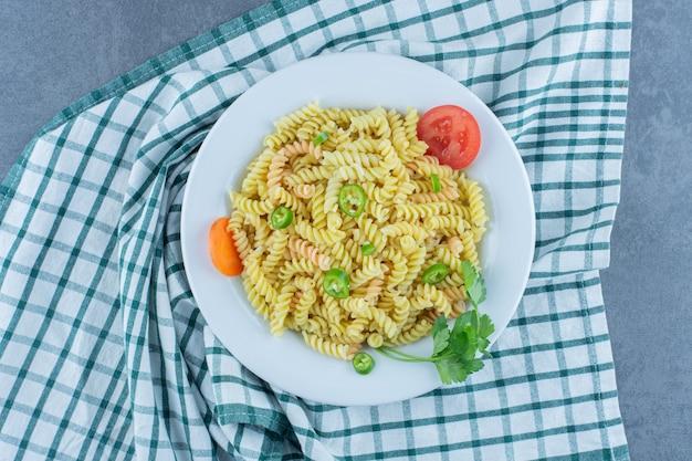 Вкусная паста фузилли с овощами на белой тарелке. Бесплатные Фотографии