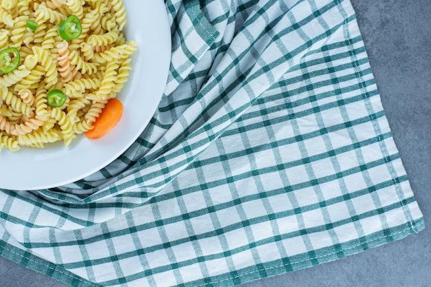 Вкусная паста фузилли с овощами на белой тарелке.